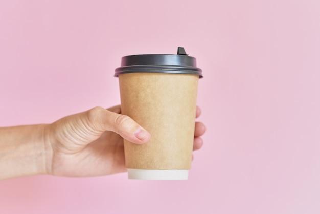 Modello della mano femminile che tiene la tazza di carta del caffè su fondo rosa.