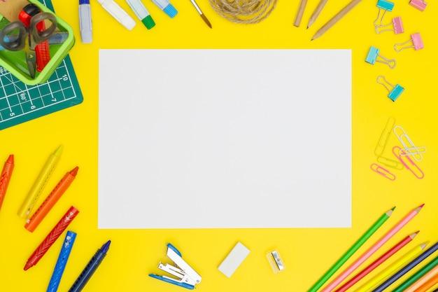 Modello della pagina della carta in bianco sulla tavola gialla con gli strumenti dell'ufficio. copia spazio