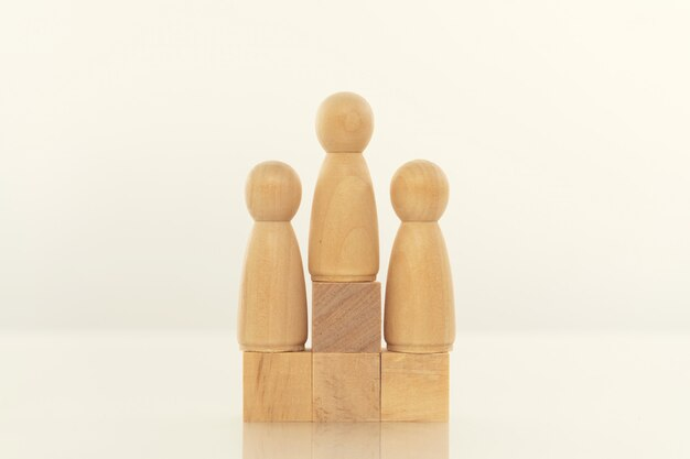 Modello della persona di legno fra la gente su bianco