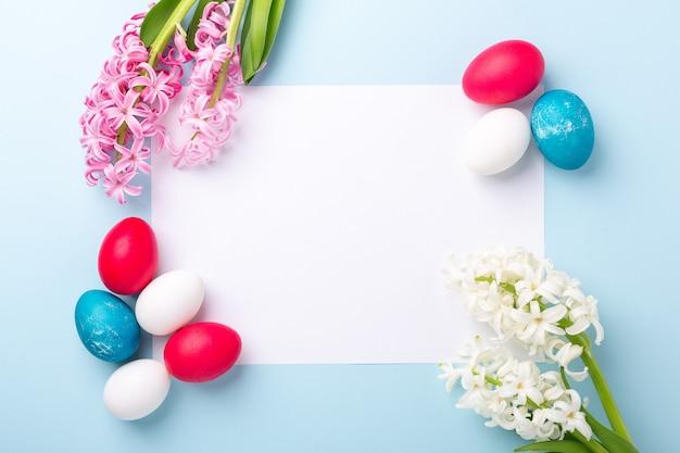 Modello della primavera con le uova di pasqua, i giacinti e lo spazio in bianco di libro bianco su fondo blu. concetto di pasqua. copia spazio. vista dall'alto