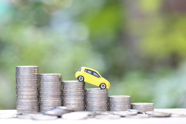 Modello di automobile gialla miniatura sulla pila crescente di soldi delle monete sul fondo di verde della natura