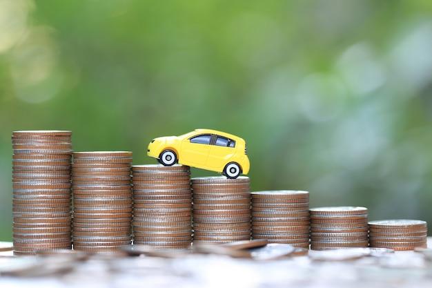 Modello di automobile gialla miniatura sulla pila crescente di soldi delle monete sulla natura