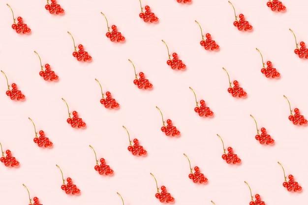 Modello di bacche. ramoscelli di bacche di ribes rosso su sfondo di carta rosa.
