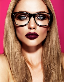 Modello di bella donna bionda calda con trucco quotidiano fresco con colore delle labbra viola scuro e pelle sana pulita in bicchieri
