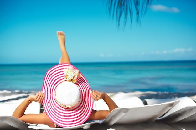 Modello di bella donna che prende il sole sulla sedia di spiaggia in bikini bianco in cappellino da sole variopinto dietro l'oceano blu dell'acqua di estate