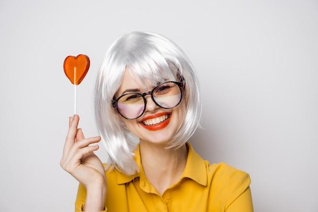 Modello di bella donna con un lecca-lecca di cuore