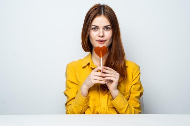Modello di bella donna con un lecca-lecca in una camicia gialla emozioni san valentino