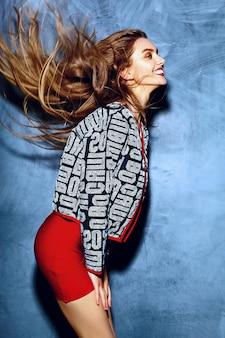 Modello di bella giovane donna bionda sorridente sexy alla moda di fascino pazzo divertente di stile di vita in panno rosso dei pantaloni a vita bassa luminosi di estate vicino alla parete grigia con i capelli di volo