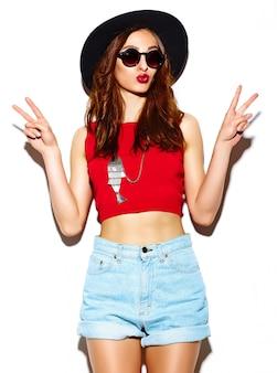 Modello di bella giovane donna sorridente sexy alla moda di fascino divertente in panno luminoso hipster estate in cappello