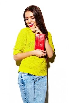 Modello di bella giovane donna sorridente sexy alla moda di look.glamor di alta moda in panno casuale giallo luminoso dei pantaloni a vita bassa di estate con la borsa della frizione