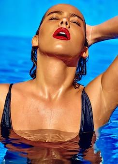 Modello di bella ragazza con i capelli scuri in costume da bagno nero