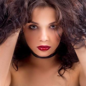 Modello di bellezza donna con lunghi capelli castani ondulati.