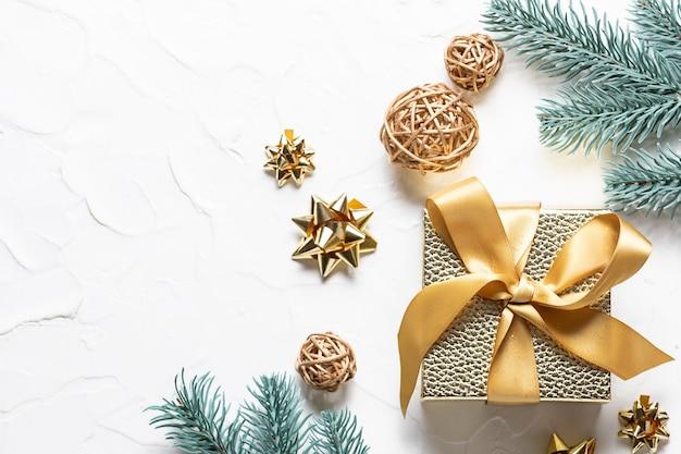 Modello di biglietto di auguri di natale con scatola regalo dorata, rami di abete e decorazioni dorate su fondo di cemento bianco.