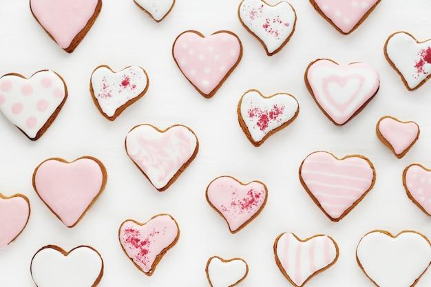 Modello di biscotti di panpepato a forma di cuore decorato con glassa bianca e rosa su una superficie di legno bianca