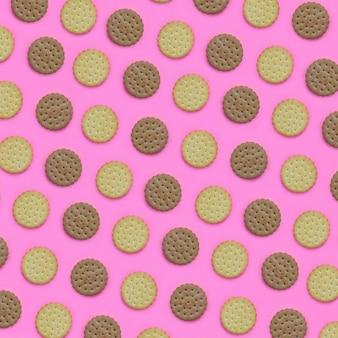 Modello di biscotti marroni su uno sfondo rosa. concetto minimalista alla moda di cibo e dessert.