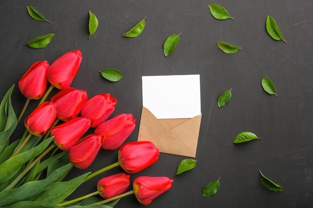 Modello di bouquet di tulipani rossi freschi e biglietto di auguri in busta di kraft e foglie sparse