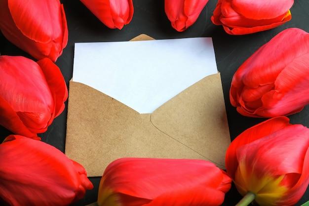 Modello di bouquet di tulipani rossi freschi e cartolina d'auguri vuota nella busta di kraft