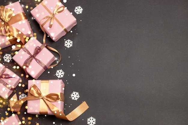 Modello di buon natale e buone feste con regali a sorpresa, nastri di atlante d'oro e neve su sfondo scuro.