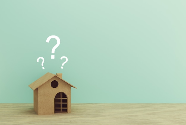 Modello di carta della casa con i punti interrogativi sulla tavola di legno con il blu. copyspace.