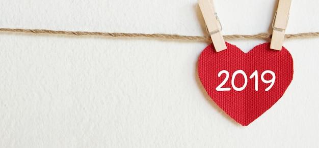 Modello di cartolina d'auguri di nuovo anno 2019, cuore di tessuto rosso con appeso parola 2019