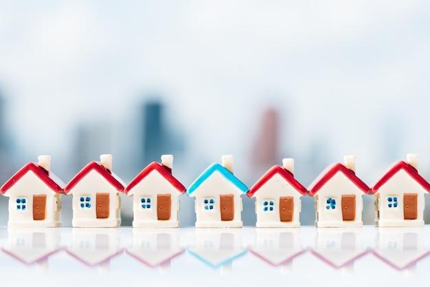Modello di casa blu tra casa rossa con sfondi della città.