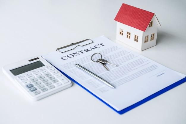 Modello di casa, calcolatrice e chiave che giace sul contratto immobiliare