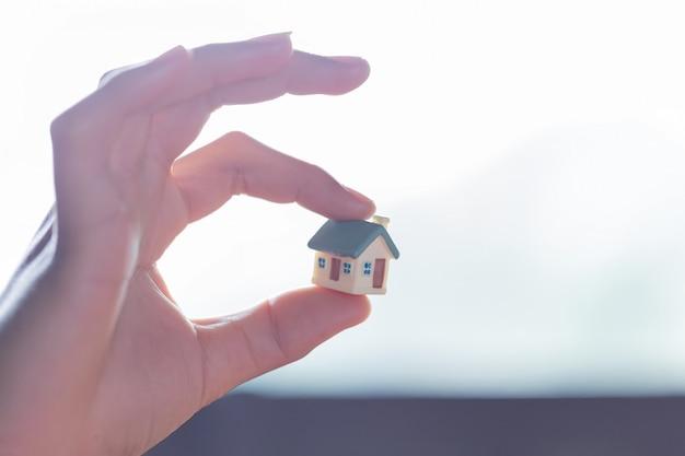 Modello di casa con la mano dell'uomo