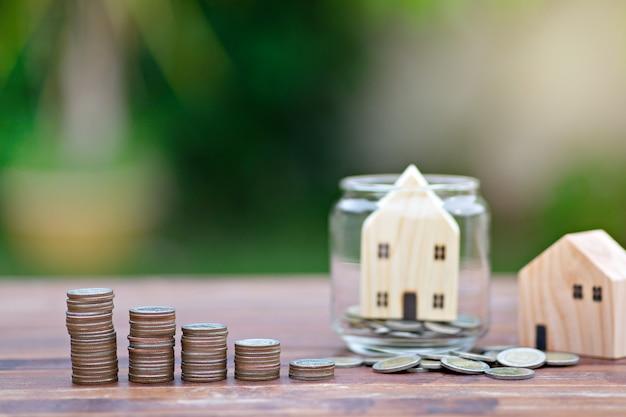 Modello di casa con pila di monete di denaro sulla tavola di legno
