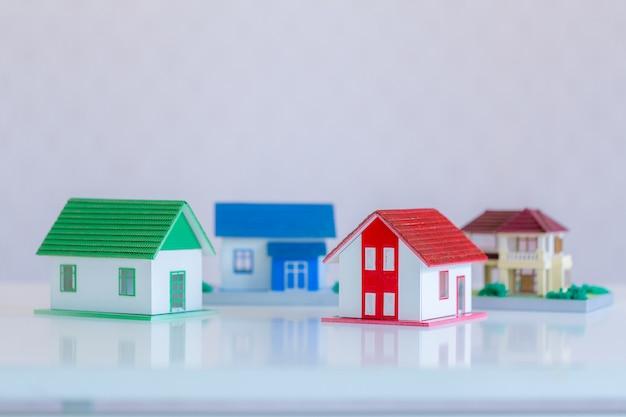 Modello di casa dipinta di bianco sotto il tetto di tegole