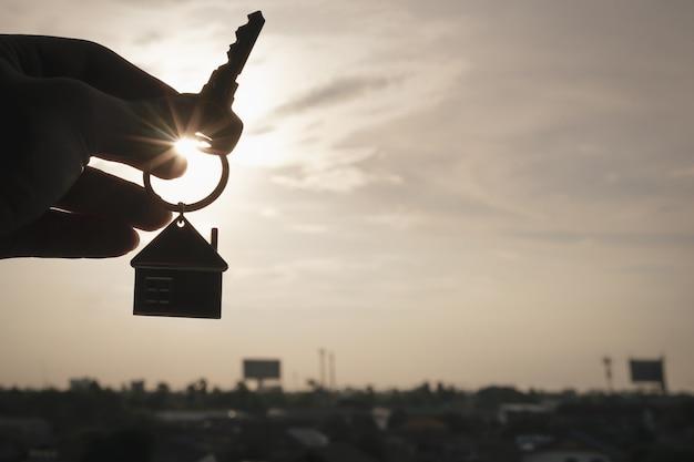 Modello di casa e chiave nella mano dell'agente di brokeraggio assicurativo domestico o nella persona del venditore.