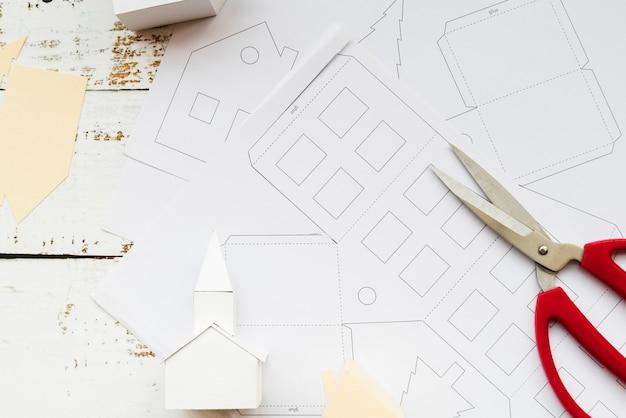 Modello di casa fatta a mano e forbice su carta bianca sopra il tavolo in legno bianco