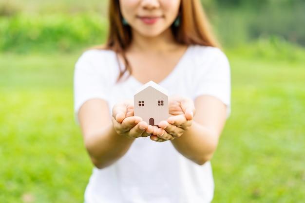 Modello di casa in legno della holding della giovane donna