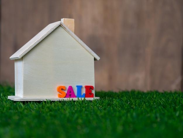 Modello di casa in legno posto su un prato verde e vendita di testo colorato sulla casa.