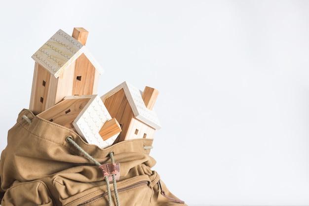 Modello di casa in miniatura nello zaino di colore marrone, concetto di investimento immobiliare, copyspace,