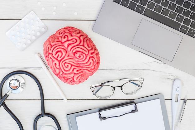 Modello di cervello rosa; pillole; stetoscopio; penna; occhiali; appunti; termometro; siringa e computer portatile sulla scrivania in legno