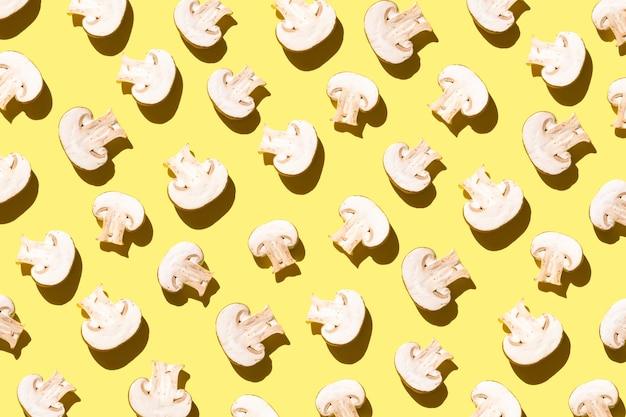 Modello di champignon tagliati su sfondo giallo chiaro