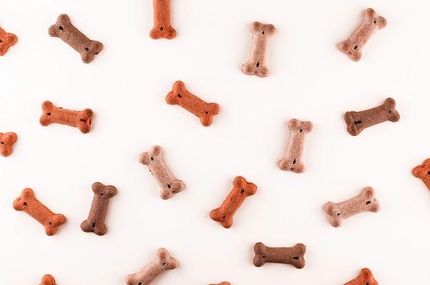 Modello di cibo per cani realizzato con spuntini secchi a forma di ossa. divertente trama piatta carino laica. animali domestici, alimentazione degli animali. dieta speciale, fornitura di allenamento.