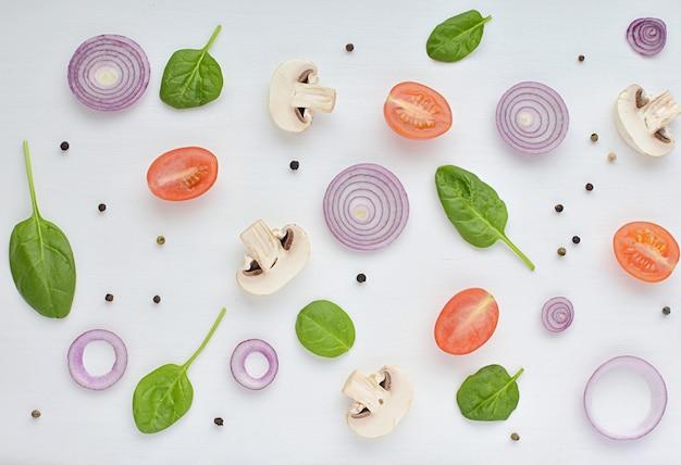 Modello di cibo vegetariano a base di cipolla rossa, pomodoro, spinaci, funghi, peperoni.