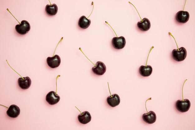 Modello di ciliegia scura sulla vista superiore del fondo rosa. distesi. stile minimal