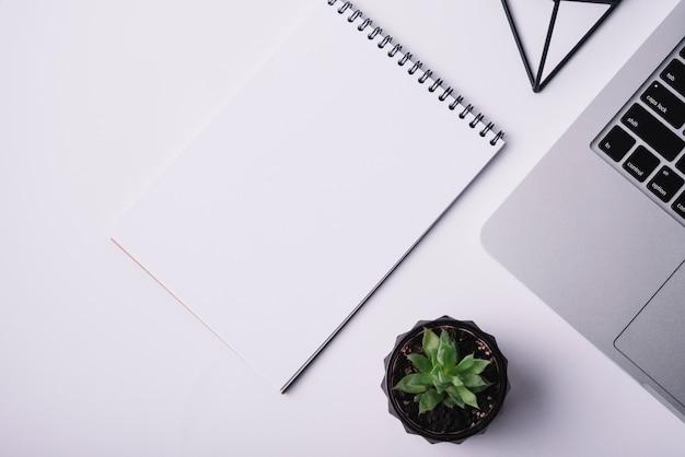 Modello di copertina del blocco note sulla scrivania con il computer portatile