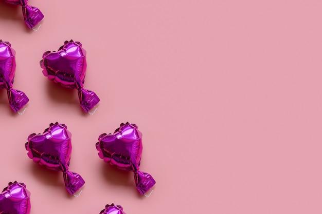 Modello di cuori palloncino foil su uno sfondo rosa