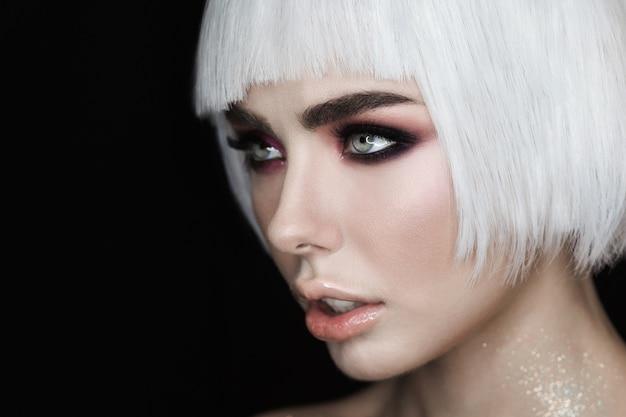 Modello di donna bionda sexy con trucco, zigomi e pelle lucida sana