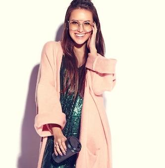 Modello di donna bruna bella hipster sorridente in elegante cappotto rosa. bevendo caffè