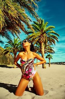 Modello di donna con i capelli scuri in bikini colorati in posa sulla spiaggia estiva