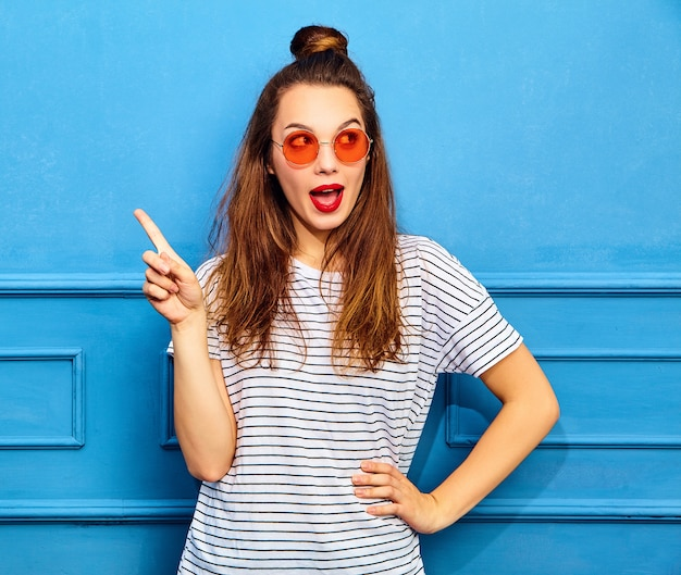 Modello di donna in abiti estivi casual con labbra rosse, in posa vicino al muro blu. tiene bene a mente come migliorare il progetto, alzare il dito, vuole suonare ed esprimere pensieri