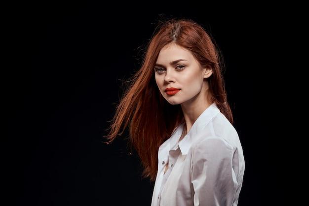 Modello di donna in jeans e una camicia bianca in posa su un muro nero