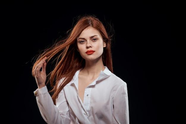 Modello di donna in posa contro il muro nero