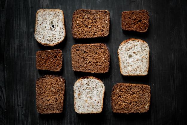 Modello di fette di pane integrale sulla superficie del legno scuro