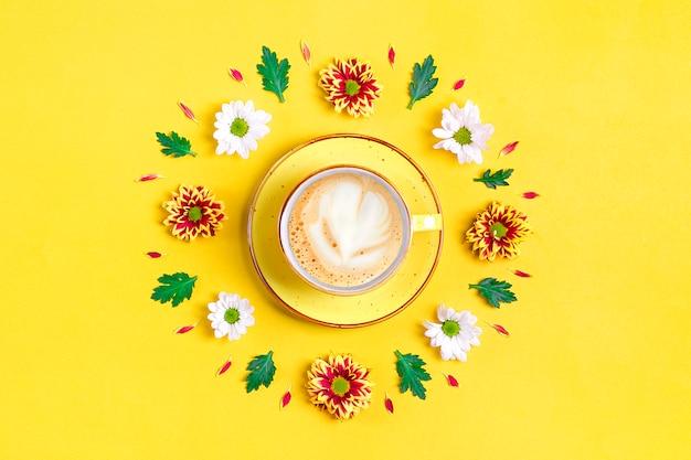 Modello di fiori di astri rossi e bianchi, foglie verdi e tazza di caffè caldo cappuccino su giallo