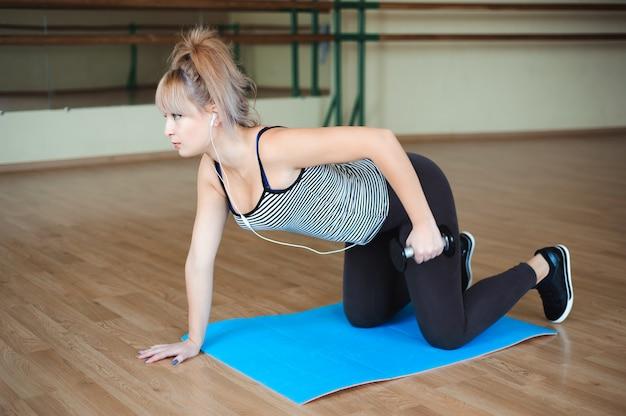 Modello di fitness facendo allenamento bodybuilding con pesi